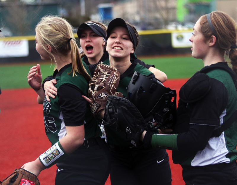 PMG PHOTO: DAN BROOD - Tigard High School softball players (from left) Sophia vanderSommen, Abby Soderquist, Maddie Hoover and Emily Paulson celebrate following a win earlier this season.