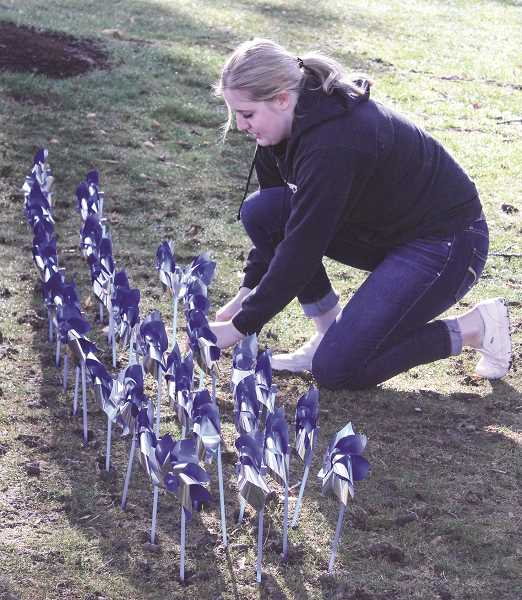 JASON CHANEY - Volunteer Kya Stafford helps plant a pinwheel garden on the Prineville Police Department lawn on Friday. Several locations were chosen for the pinwheels to raise awareness of Child Abuse Prevention Month.