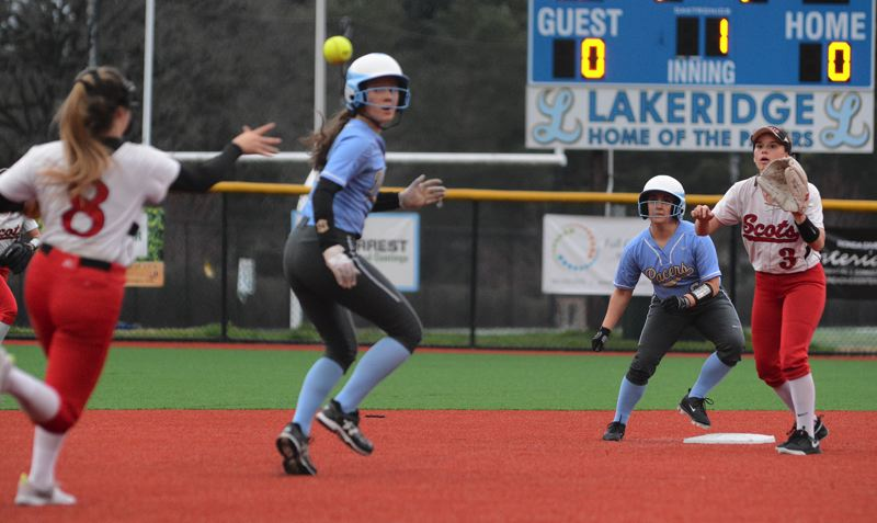 PMG PHOTO: DAVID BALL - David Douglas Lilly Center (3) awaits a throw from teammate Bailey Haga while catching Lakeridge runner Summer Mickey in a hot box in the first inning.