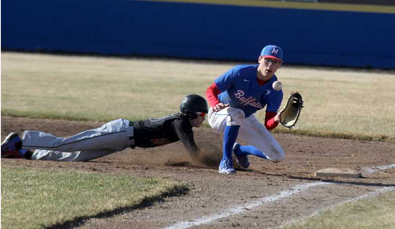 STEELE HAUGEN - Madras first baseman Reece White focuses on catching the ball, while Culver's Trevor Smith dives head first back to the base.