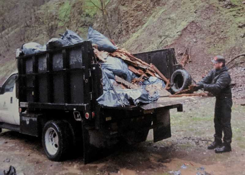 COURTESY PHOTO - A participant in the 36 Pit Cleanup several years ago prepares to take away trash gathered during the event.