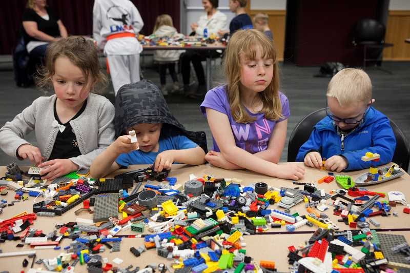 PMG PHOTO/JAIME VALDEZ - Neighborhood kids Emry Young,5, left, Toby Fumasi,5, Elyse Fumasi,6, and Jace Evens,5, make their creations at Lego night at the Wilsonville Library.