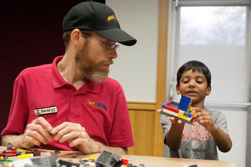 PMG PHOTO/JAIME VALDEZ - David Thornton, with Bricks Minifigs watches Ian Brown,6, show off his creation during Lego night at the Wilsonville Library.