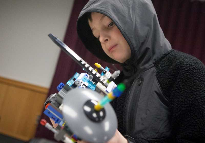 PMG PHOTO/JAIME VALDEZ - Ian Northcutt,6, works on his project during Lego night at the Wilsonville Library.
