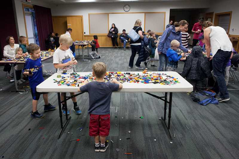 PMG PHOTO/JAIME VALDEZ - Children and their parents participate in Lego night at the Wilsonville Library.