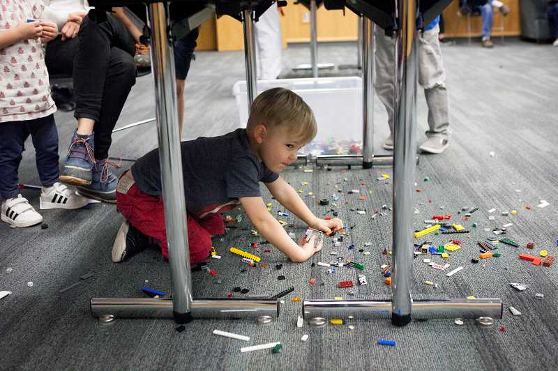 PMG PHOTO/JAIME VALDEZ - Micah Dixon,4, looks under the table for Lego pieces during Lego night at the Wilsonville Library.
