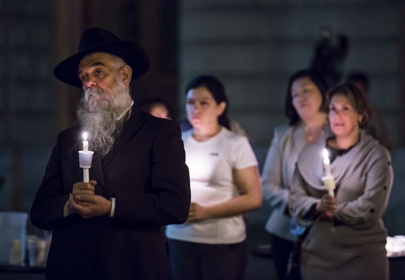 PMG FILE PHOTO - Rabbi Moshe Wilheim stands with mourners during an October 2015 candlelight vigil at City Hall for the victims of the Umpqua Community College shootings.