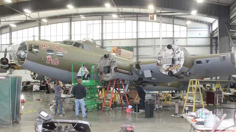 PHOTO BY SUSAN MATHENY - Crews work on winter maintenance for the B-17 bomber that was formerly called 'Madras Maiden,' and is now called 'Ye Olde Pub.' The former name and paint will eventually be restored.