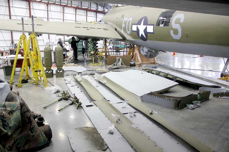 PHOTO BY SUSAN MATHENY - Workers perform winter maintenance on Erickson Aircraft Collection's B-17 bomber. The aircraft has been on loan to the Liberty Foundation, which leases the plane for much of the year.