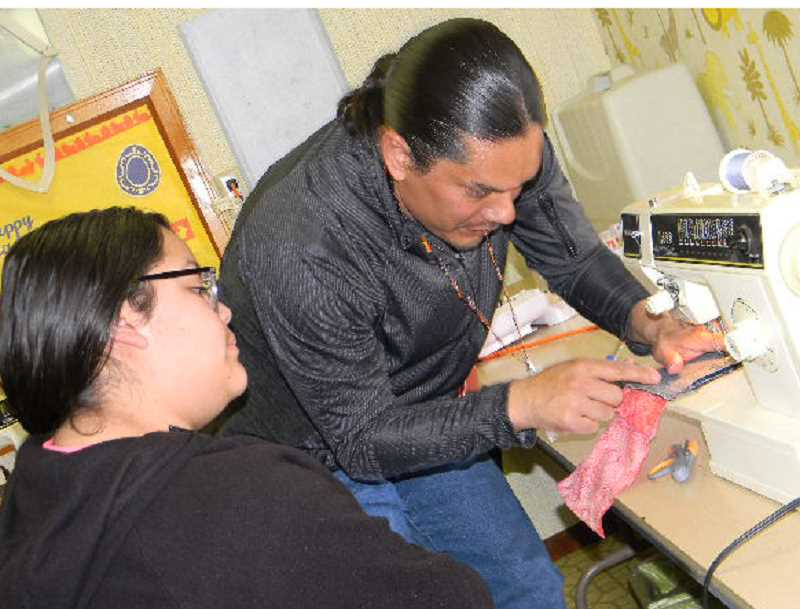 SUBMITTED PHOTO - At left, Alyssa Castaneda watches as John Courtney shows her how to use a sewing machine.