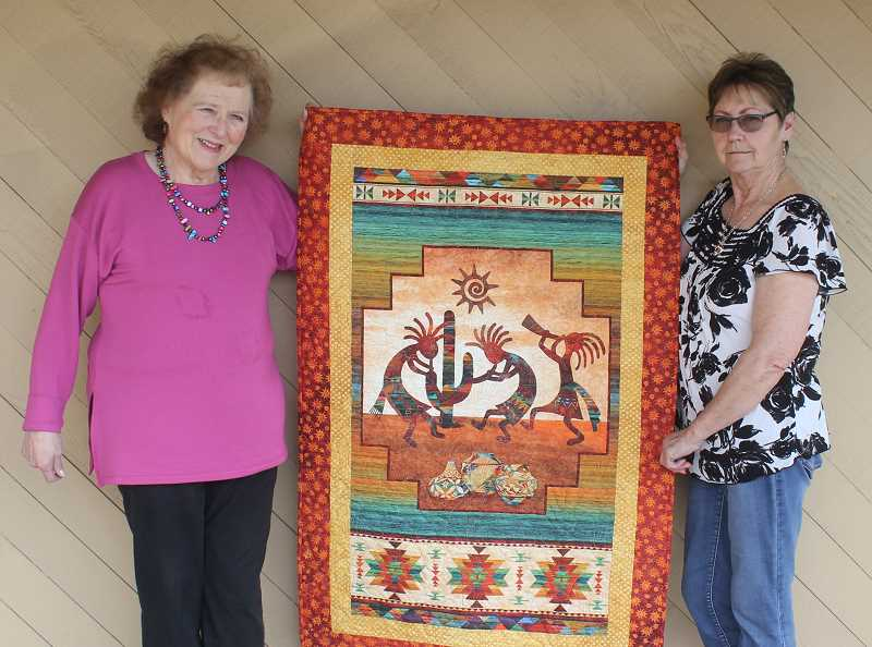 DESIREE BERGSTROM/MADRAS PIONEER - Joanne Heare, left and Becky Jordan display one of the Country Quilters of Jefferson County's quilts, which will be on display at the 14th biennial Quilt Show at the Jefferson County Fairgrounds April 13-14.