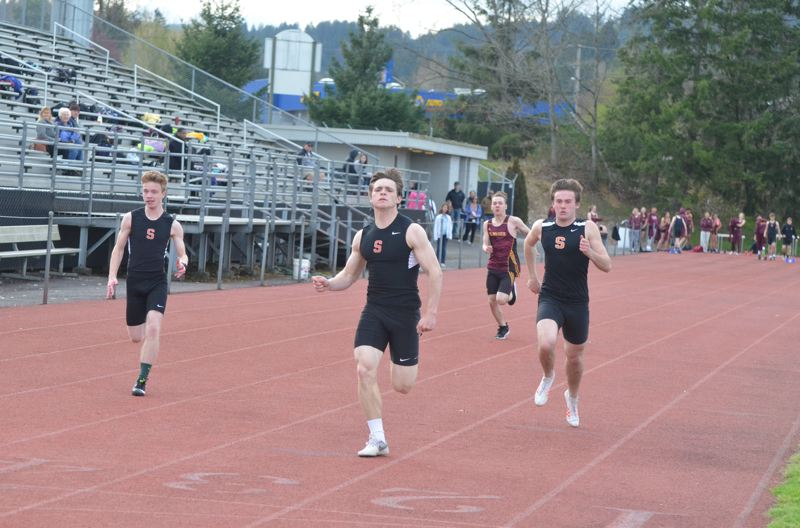 COURTESY PHOTO: JOHN BREWINGTON - Connor McNabb (center) leads Scappoose teammates Tyler Holcomb (right) and Henry Goldammer to a sweep of the 100 meters.