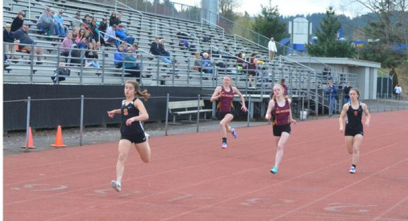 COURTESY PHOTO: JOHN BREWINGTON - In her first 100-meter dash, Tess Conway (left) is out front at the finish for the Scappoose Indians.