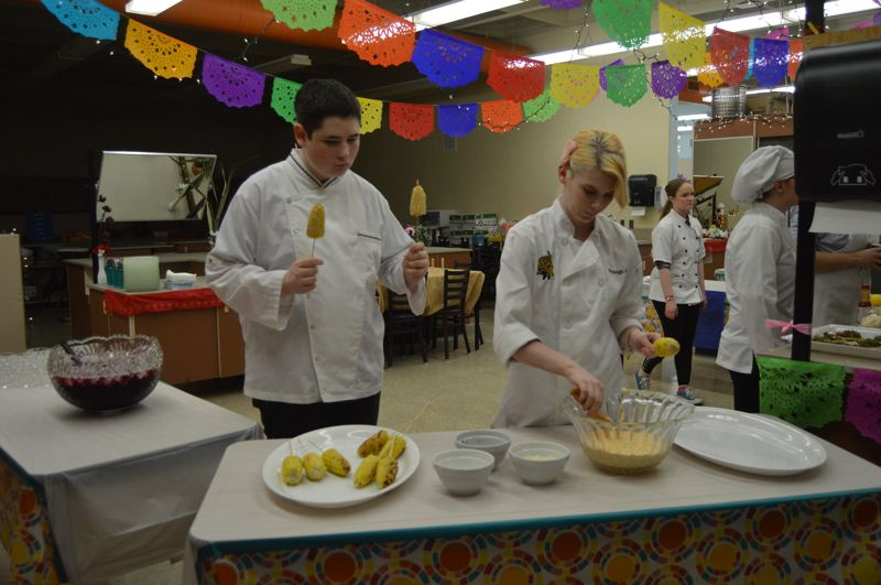 PMG PHOTO: NICOLE THILL-PACHECO - Students prep grilled corn and other toppings before a teacher cafe in late March. Students decorated the classroom to resemble a Mexican street fair.