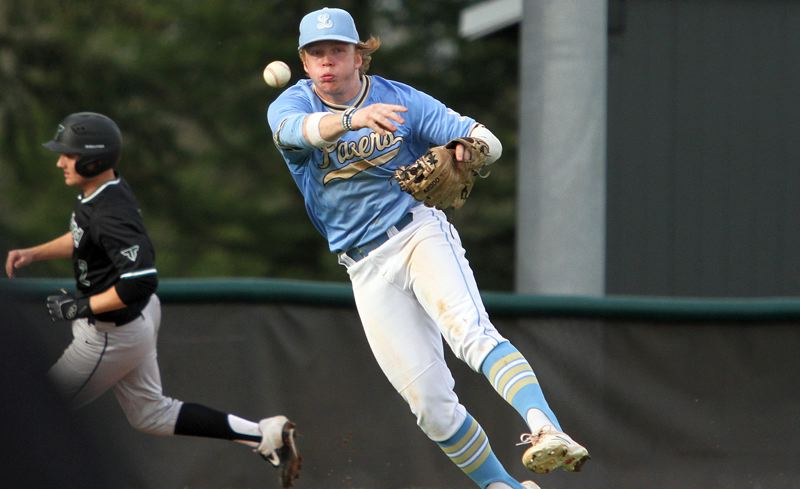 PMG PHOTO: MILES VANCE - Lakeridge third baseman Brian Hamlin makes a barehanded pickup and throw for an out during his team's 3-2 loss to Tigard in eight innings at Lakeridge High School Wednesday, April 3.