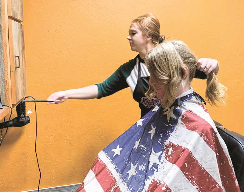 PHOTO COURTESY OF JANE SCHEPPKE   - Crook County Library Executive Director Buzzy Nielsen follows through on the Love the Locks or Buzz Them Off challenge results Wednesday afternoon. The Buzz Them Off donations won, so Nielsen dutifully went to Cougar Cuts for his haircut.