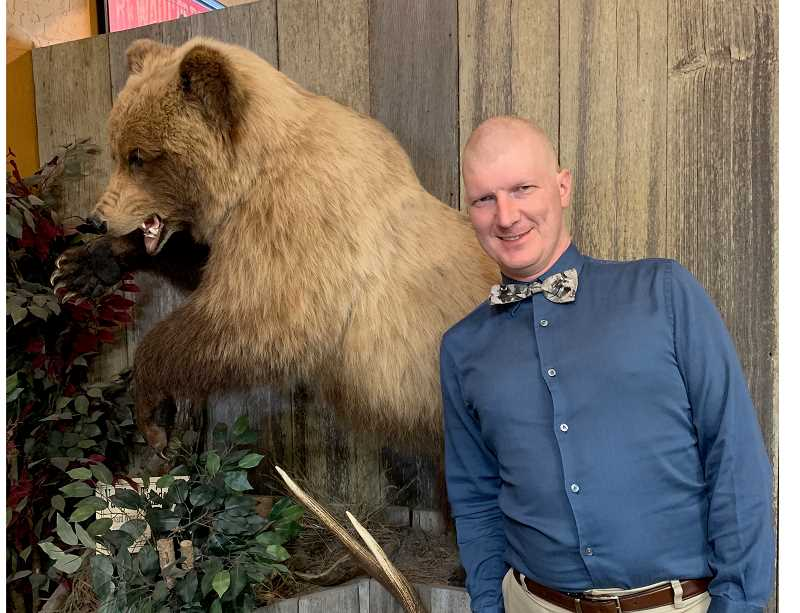 PHOTO COURTESY OF JANE SCHEPPKE  - Bare and a bear: Crook County Library Executive Director Buzzy Nielsen shows off his recently buzzed head.