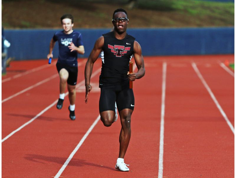 PMG PHOTO: DAN BROOD - Tualatin High School senior Kwabena Lynn, shown here in the 4 x 100 relay, was a four-time winner in the Wolves TRL dual meet victory at Lake Oswego.