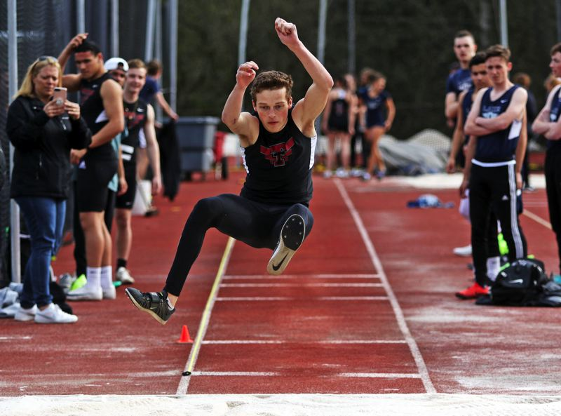 PMG PHOTO: DAN BROOD - Tualatin High School senior Jalen Hale triumphed in the long jump with a mark of 20-8 during the Timberwolves' TRL dual meet win at Lake Oswego.