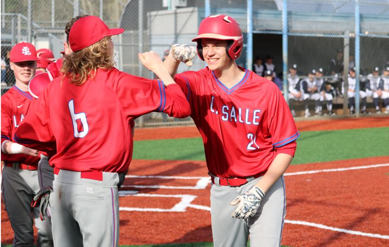 PMG PHOTO: JIM BESEDA - La Salle Prep's Gavin Gately (21) is all smiles as he is greeted by teammates after his three-run home in the first inning of Friday's Northwest Oregon Conference road game against Wilsonville.