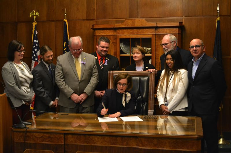 PMG PHOTO: MARK MILLER - Gov. Kate Brown signs into law a ban on oil and gas drilling off Oregon's coastline on Wednesday, March 27.