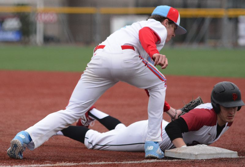 PMG PHOTO: DAVID BALL - Centennial first baseman Landan Fery reaches for the tag on Sandys Colby Carson in the seventh inning of Thursdays 1-0 road win.