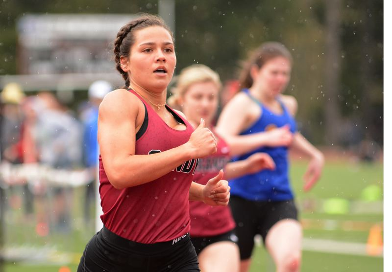 PMG PHOTO: DAVID BALL - Sandys Marley Salveter comes through the finish line with a win in the 100-meter dash at Saturdays Sandy Invitational. She also won the 200 later in the day.