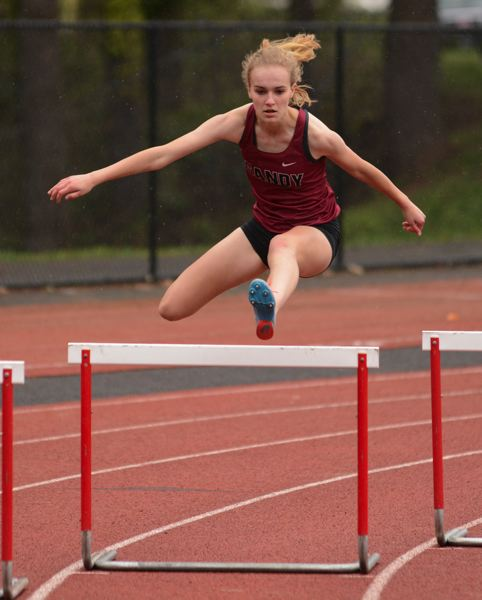 PMG PHOTO: DAVID BALL - Sandys Adilynn Brotnov clears a corner hurdle on her way to second place in the 300-meter hurdles.