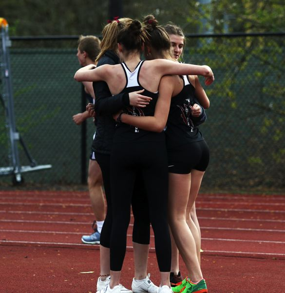 PMG PHOTO: DAN BROOD - Tualatin's four high jumpers have a group hug during the Timberwolves meet at Lake Oswego last week.