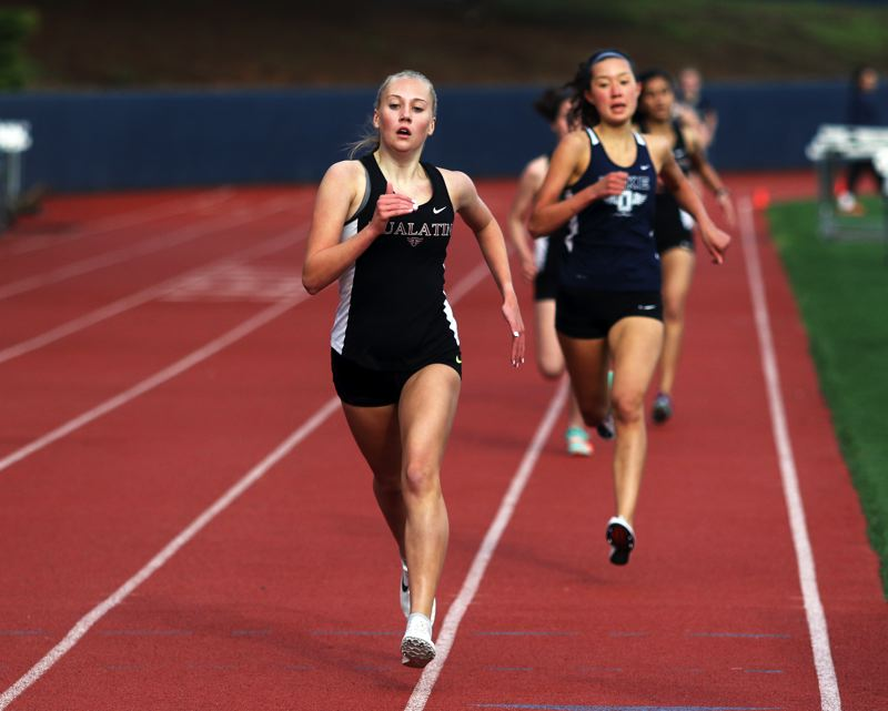 PMG PHOTO: DAN BROOD - Tualatin freshman Paige Olson used a strong finish to take first place in the 1,500-meter run during the Wolves' dual meet win at Lake Oswego.