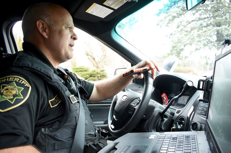 PMG PHOTO: MATT DEBOW - Deputy Joe Rocky Graziano calls a complainant from his patrol car on Thursday, April 4, to the inform the caller what he discovered after investigating the situation.
