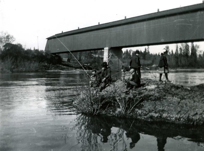 COURTESY PHOTO - A group fishes on the Clackamas River beneath the railroad bridge in Gladstone around the year 1900.