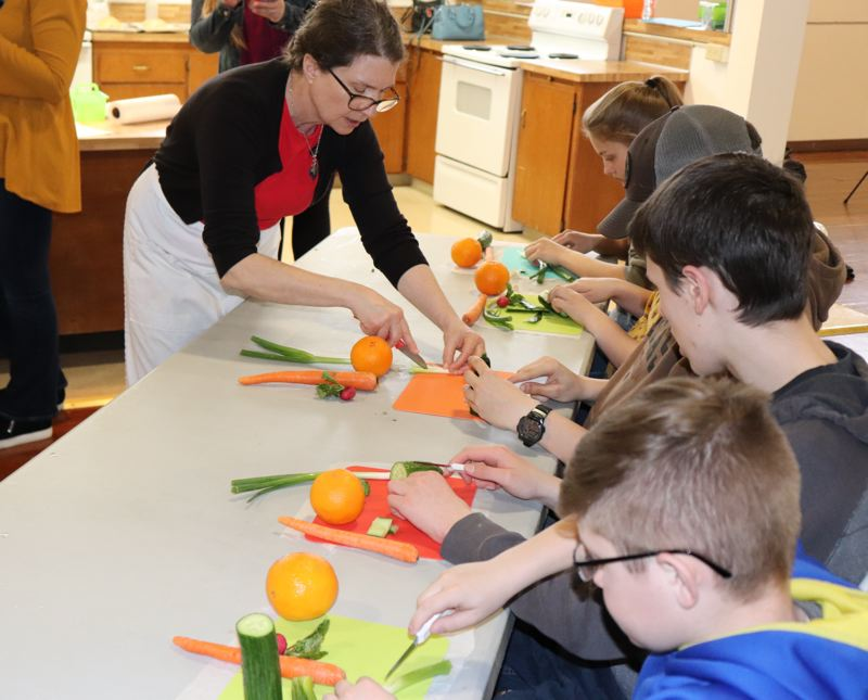 COURTESY PHOTO: KIMBERLY JACOBSEN NELSON - 4-H alumna Jane Eilert teaches 4-H Juniors knife safety and cutting skills at 4-H Spring Break Camp.