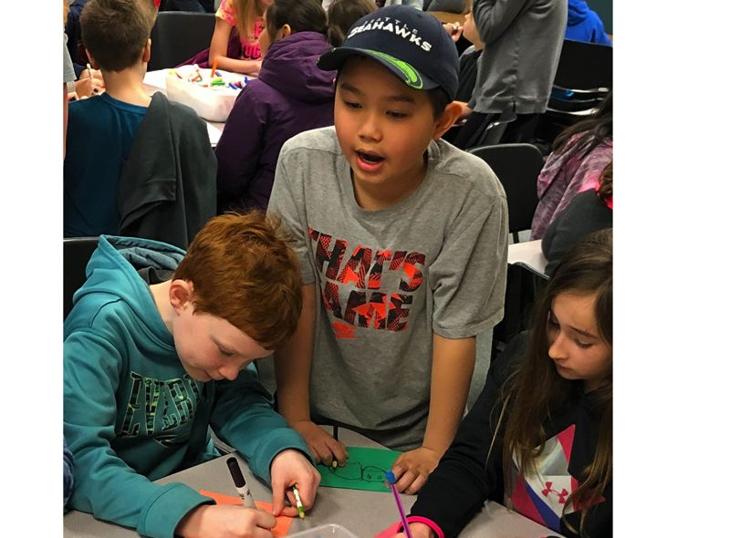 Aidan Frerichs (from left), Evan Pong and Isabella Di Francisco, fifth-graders at Beavercreek Elementary, work on illustrations of their school song for a book music teacher and children's author Andy Morrow is creating.