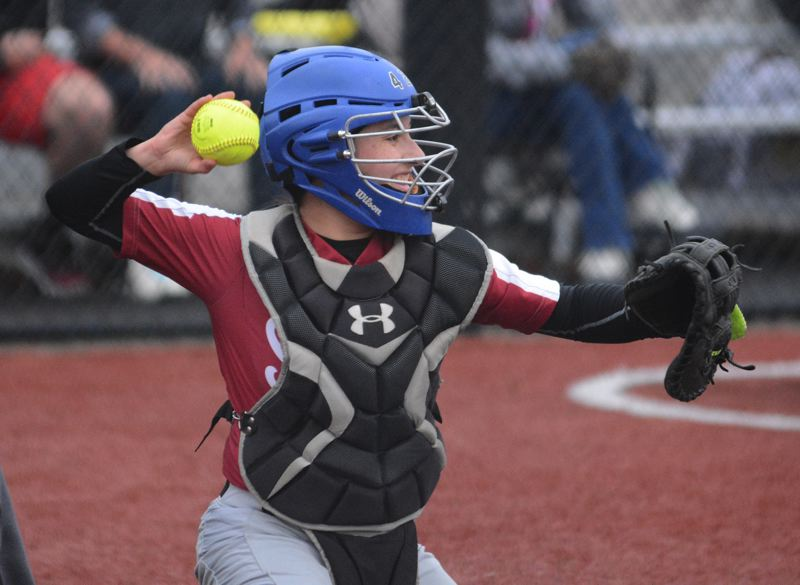 PMG PHOTO: DAVID BALL - Sandy catcher Alejandra Ortega fires the ball back to the pitchers circle during the Pioneers 12-11 win over Corvallis on Thursday.