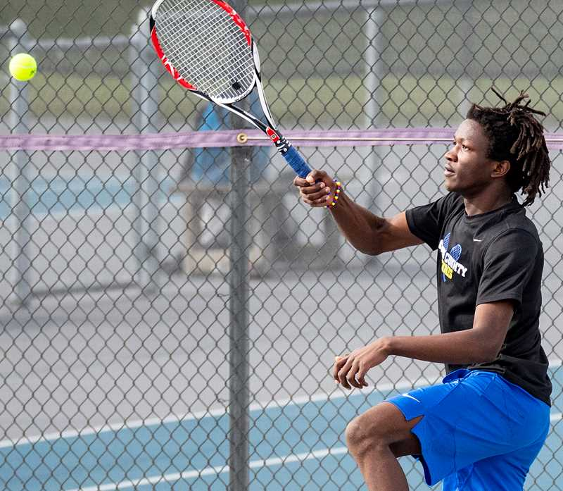LON AUSTIN/CENTRAL OREGONIAN - Moses Freauff follows through after hitting a shot on Thursday against Ridgeview. Freauff easily won his match. Then on Saturday, Freauff went 6-1 at a tournament in Madras.