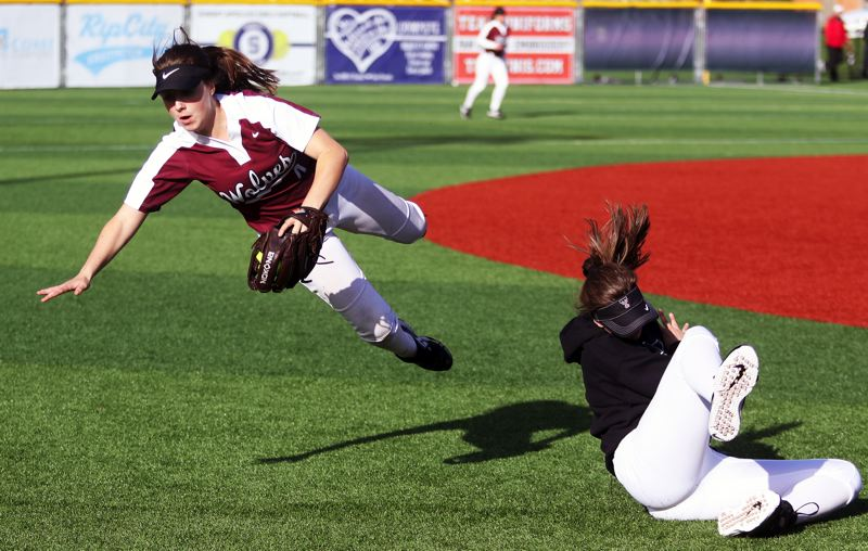 PMG PHOTO: DAN BROOD - Tualatin junior shortstop Bella Valdes (left) catches a fly ball while crashing into junior left fielder Savannah Braun during Friday's game at Sunset.