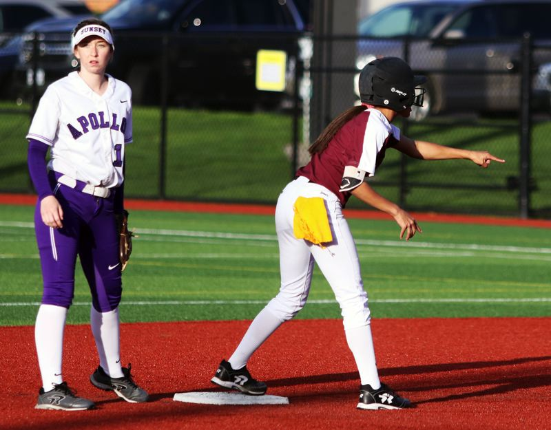 PMG PHOTO: DAN BROOD - Tualatin junior Tia Ridings (right) points back to the Timberwolf dugout after hitting an RBI double during the seventh inning of Friday's game at Sunset.
