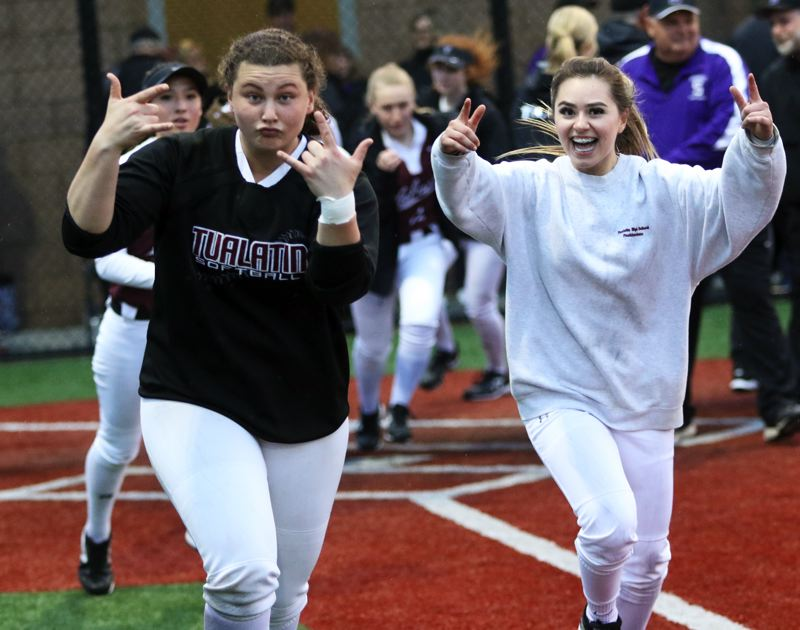PMG PHOTO: DAN BROOD - Tualatin seniors Emily Johansen (left) and Andrea Gomez celebrate following the Timberwolves' 7-6 10-inning win at Sunset on Friday.