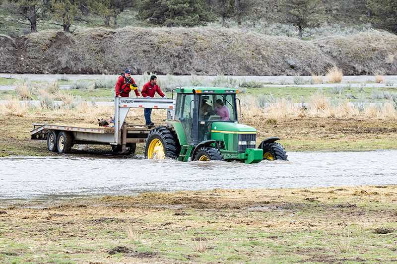 LON AUSTIN/CENTRAL OREGONIAN - Crook County Sheriff's deputies and fire personnel were driven across the first Crooked River crossing by a ranch tractor.