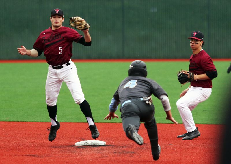 PMG PHOTO: DAN BROOD - Tualatin senior shortstop Kyle Dernedde (left) gets ready to tag out Lakeridge senior Casey Smith during Monday's game.