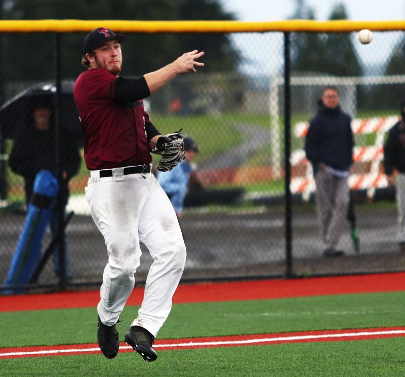 PMG PHOTO: DAN BROOD - Tualatin senior third baseman Gavin Moore makes a throw to first base during the Wolves' 5-3 win over Lakeridge on Monday.