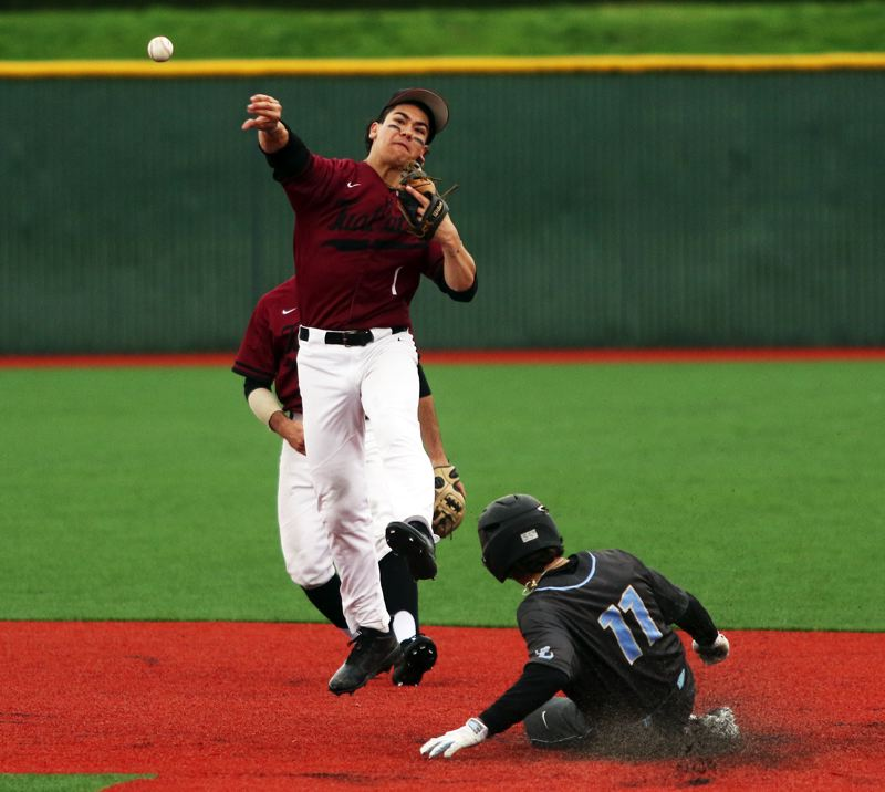PMG PHOTO: DAN BROOD - Tualatin senior second baseman Jett Searle makes a throw to first base on a double-play attempt during the Wolves' 5-3 win over Lakeridge on Monday.