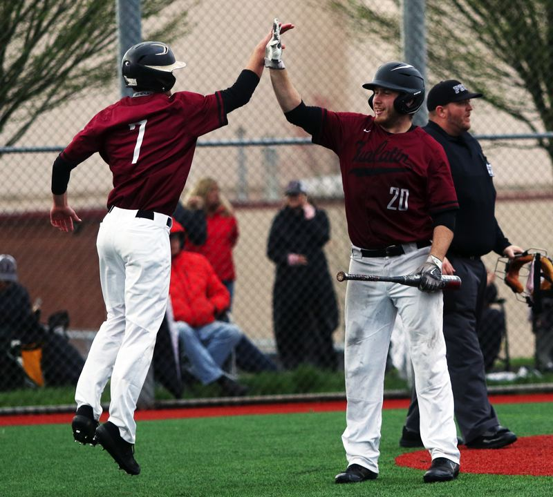 PMG PHOTO: DAN BROOD - Tualatin junior Blake Jackson (left) and senior Gavin Moore celebrate after Jackson scored a run in the Wolves' 5-3 win over Lakeridge on Monday.