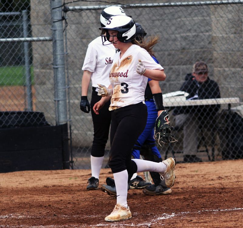 PMG PHOTO: DAN BROOD - Sherwood High School junior Emily Knott comes in to score a run during the team's 11-0 win over Gresham on Tuesday.