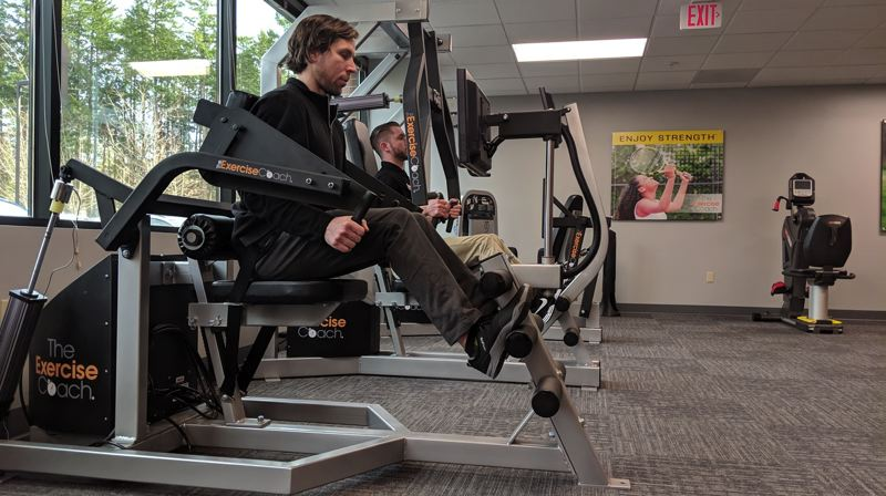 PAMPLIN MEDIA: JOSEPH GALLIVAN  - Trainers Preston McCann (left) and Tyler Wood show how to use the Exerbotics machines at the Exercise Coach, a new, high-tech gym in Lake Oswego. You should be in an out in 30 minutes for about $50.
