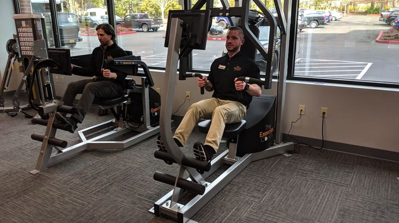 PAMPLIN MEDIA GROUP: JOSEPH GALLIVAN  - Trainers Preston McCann (left) and Tyler Wood show how to use the Exerbotics machines at the Exercise Coach, a new, high-tech gym in Lake Oswego. You should be in an out in 30 minutes for about $50.