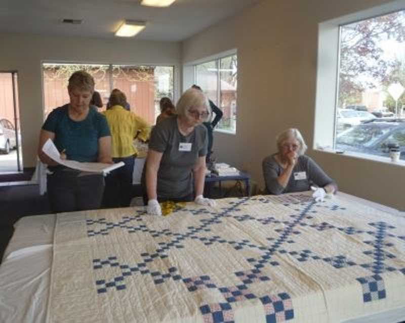 Volunteers inspecting a quilt at Oregon Quilt Project documentation day.