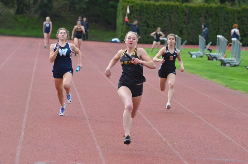 PMG PHOTO: JOHN BREWINGTON - Savannah Moore (middle) crosses the finish line first in the girls 4x100-meter relay Wednesday at Scappoose, with Wilsonville second and Tess Conway (right) and the host Indians third.