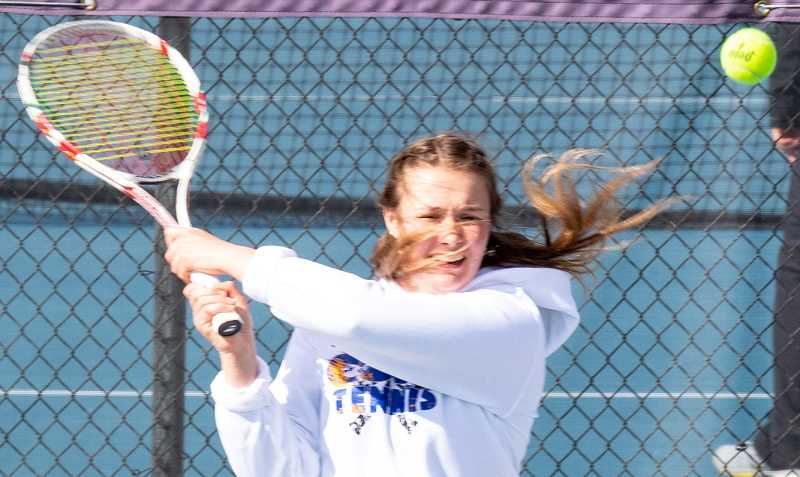 LON AUSTIN/CENTRAL OREGONIAN - Tansy Clark follows through after hitting a backhand shot against Redmond on Tuesday. Clark and her doubles partner Marlen Ceja won their No. 1 doubles match 6-1, 6-4 for one of just two Crook County wins in the dual.